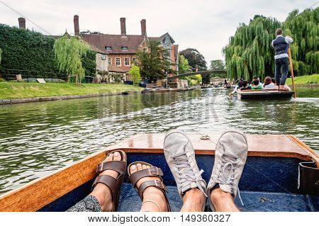 Man and woman feet on a boat punting in the river in Cambridge. Focus on feet.