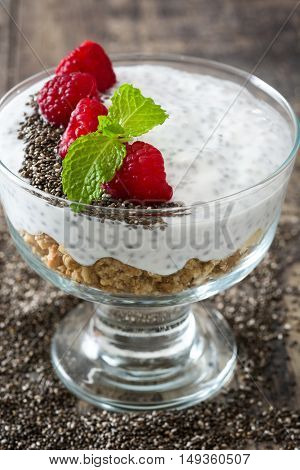 Chia yogurt with raspberries and chia seeds on wooden table