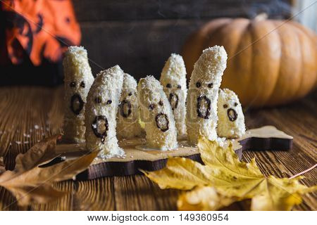 Homemade halloween scary banana ghosts monsters with chocolate faces. funny dessert recipe for party decoration fruits on vintage wooden table background