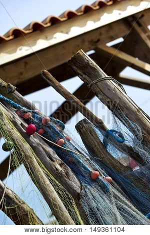 Fishing nets and buoys hanging on wooden stakes front of a fisherman's hut