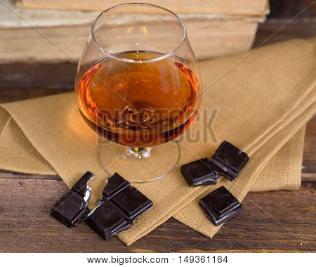Glass of brandy and a chocolate on a old wooden table with old books