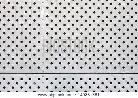 Perforated silver metal surface, an industrial background.