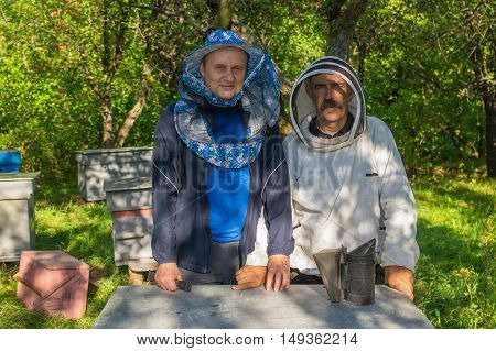 Portrain of Ukrainian bee-keeper and his assistant at work place