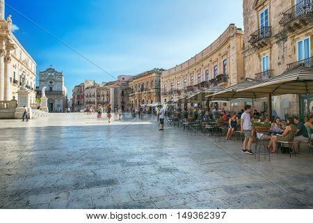 SYRACUSE, ITALY - JUL 26, 2016: tourists and locals visit the main square and a local restaurant at the Piazza del Duomo in Ortigia, Syracuse, Italy. Historical center of Syracuse, Sicily.