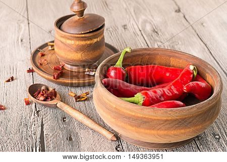 Pepper bitter, fresh and dried chopped, in a wooden cookware on a gray wooden table.