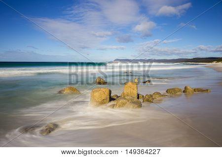 Waves in a calm sea break against the rocks on a beach called Friendly Beaches in Freycinet National Park, Tasmania
