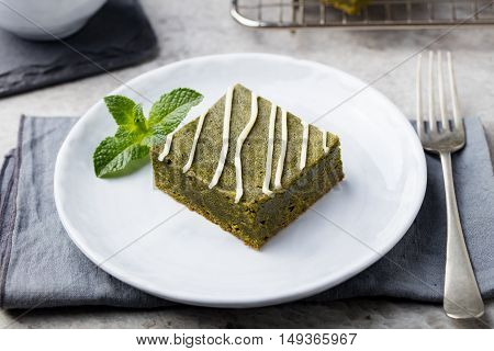 Matcha green tea brownie dessert with white chocolate on a white plate Grey stone background.