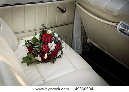 wedding bouquet of red and white roses on the back seat of the car