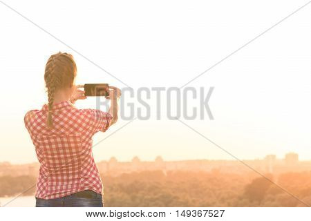 Rear view of female taking photo of city buildings from hill by using touch screen smart phone.
