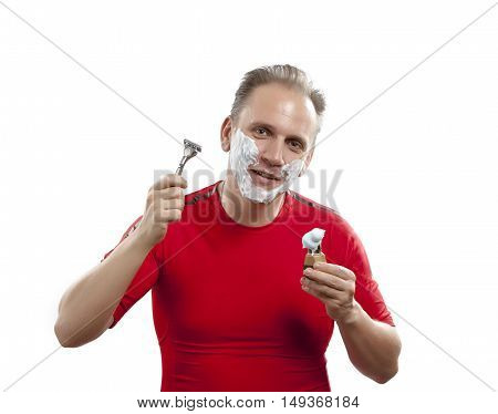 man has a shave- with the razor and a small brush