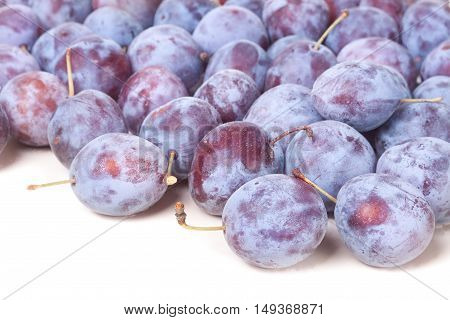 heap of blue plums isolated on a white background.