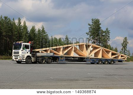 ORIVESI, FINLAND - SEPTEMBER 1, 2016: White MAN TGA 26.430 semi truck transports roof truss on flat trailer.