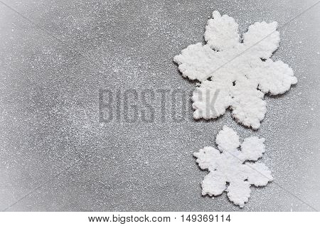 Two white fabric suspended snowflakes on grey background