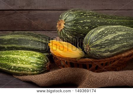 green zucchini or courgettes with a flower on sackcloth wooden background.