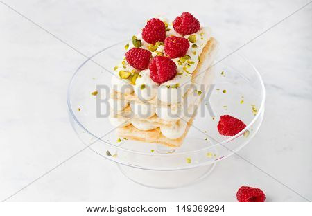 Millefeuille, Mille Feuille cake with fresh raspberries and pistachio nuts on a transparent cake stand on a white background. Copy space