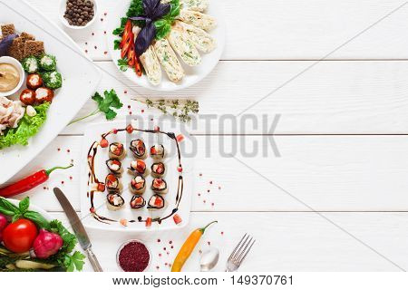 Tasty appetizing snacks, flat lay, free space. Variety of various food on white wooden background, copy space for text
