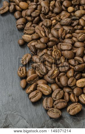 Coffee beans on a wooden spoon on a background of coffee