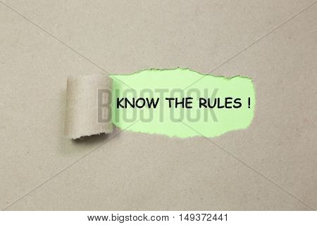 The text KNOW THE RULES behind torn paper