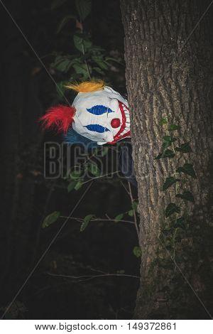 scary clown behind tree in park night scene