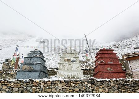 Three stone stupas under Thorong La pas in winter. Annapurna region in Nepal.