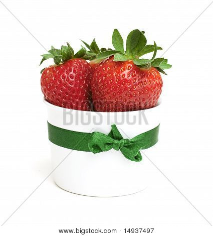 fresh strawberries in a white dish tied with a ribbon