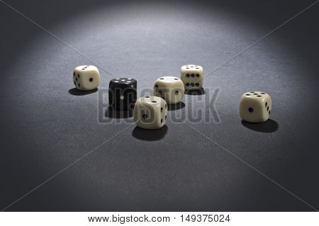 White and black gambling dices on dark background.
