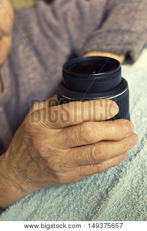 Old Hand holdind camera dslr lens on table