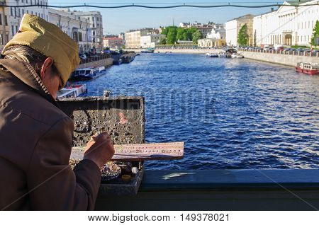 St. Petersburg Russia - May 22 2014: a street artist paints river landscape on the bridge over the Neva River.