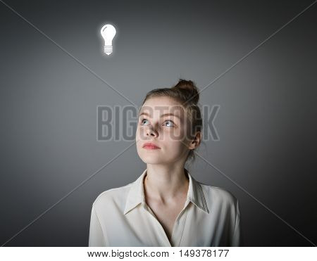 Girl in white having an idea with light bulb over her head.