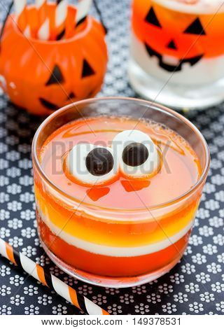 Fun food for kids - jelly with eyes on Halloween. Orange yellow and white candy corn jello in a glass