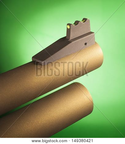 Fiber optic front sight on a gold colored shotgun with a green background
