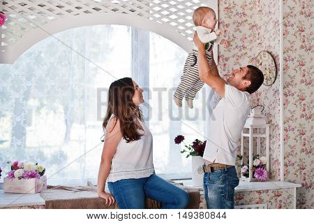 Young Caucasian Happy Family. Father Throws Baby In His Arms