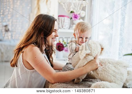 Cute Caucasian Baby Boy Sitting On Windowsill And Play With Mother Soft Toy Dog