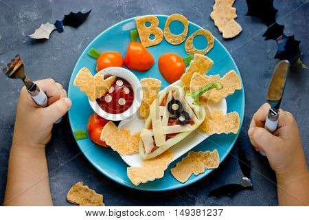 Child eat colorful vegetarian dinner or lunch in Halloween style. Creative idea for schoolboy food. Fun with food consept top view
