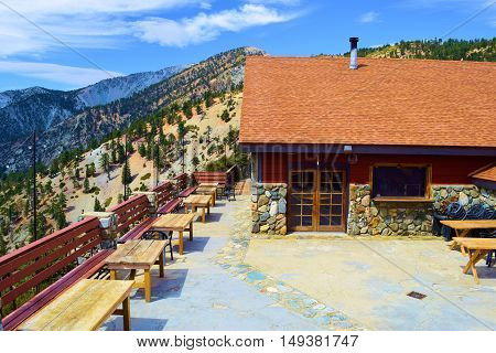 September 26, 2016 in Mt Baldy, CA:  Outdoor furniture with a rustic vibe overlooking mountains taken at The Mt Baldy Notch Lodge courtyard patio where customers can have a drink and a meal with amazing views taken in Mt Baldy, CA