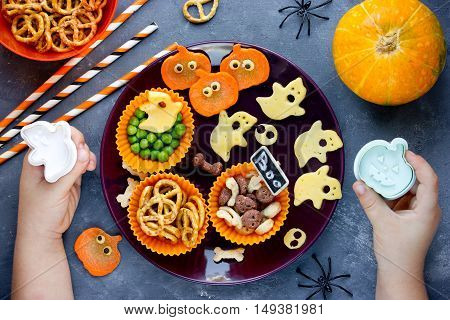 Assortment of traditional snacks for Halloween. Child on kitchen prepare funny food for Halloween treats. Happy halloween food composition