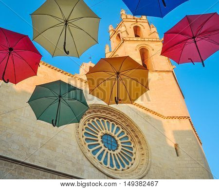 Colored Umbrellas Against Gothic Cathedral.