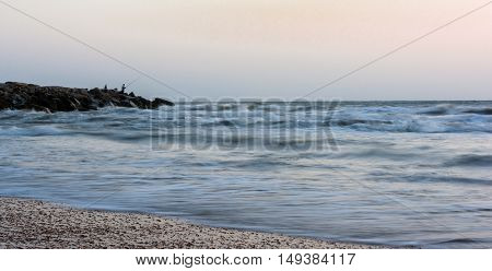 the fishermen catch fish from the seashore at sunrise