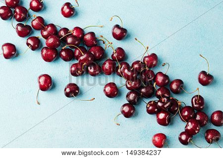 Fresh ripe black cherries on a blue stone background Top view Copy space.