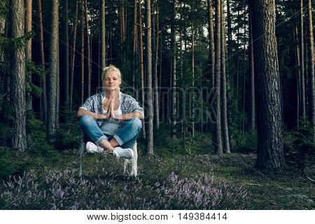 Young beautiful woman meditating and levitating in the forest.Relaxed lifestyle.