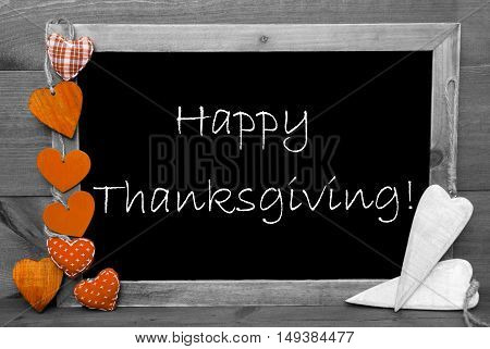 Chalkboard With English Text Happy Thanksgiving. Orange Hearts. Wooden Background With Vintage Rustic Or Retro Style. Black And White Image With Colored Hot Spots.