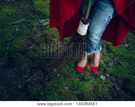 Witch legs in red shoes standing in the woods with a broom in his hand.Halloween holiday.
