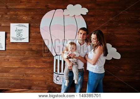 Young Caucasian Happy Family In Love Background Wooden Room With Air Balloon Decor.