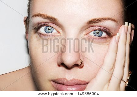 Young blue eyes woman touching her face