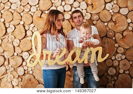 Young Caucasian Happy Family  Background Wooden Stump Wall With Word Dream At Hands