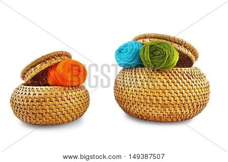 Two wicker boxes with yellow thread on a white background
