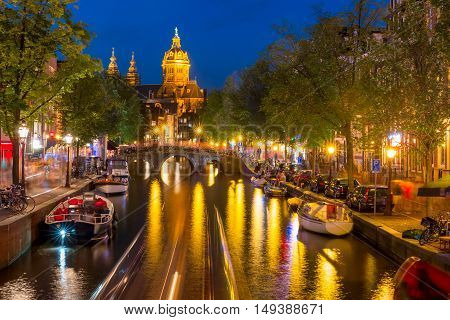 Night red-light district De Wallen, canal, Basilica of Saint Nicholas and bridge, Amsterdam, Holland, Netherlands. Long exposure.
