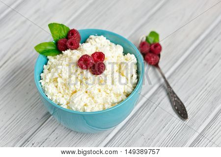 Cottage Cheese In Blue Bowl With Raspberries And Mint On Wooden Background Napkin