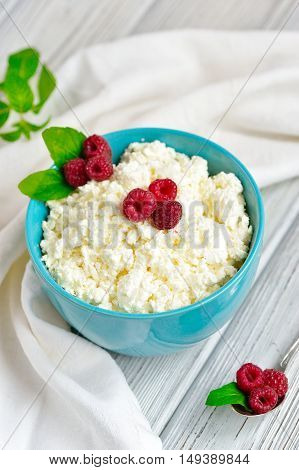 Cottage Cheese In Blue Bowl With Raspberries And Mint On Wooden Background