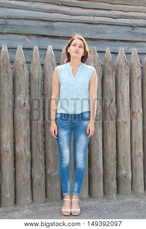 Young beautiful girl looking to the top on a background of wooden fence.